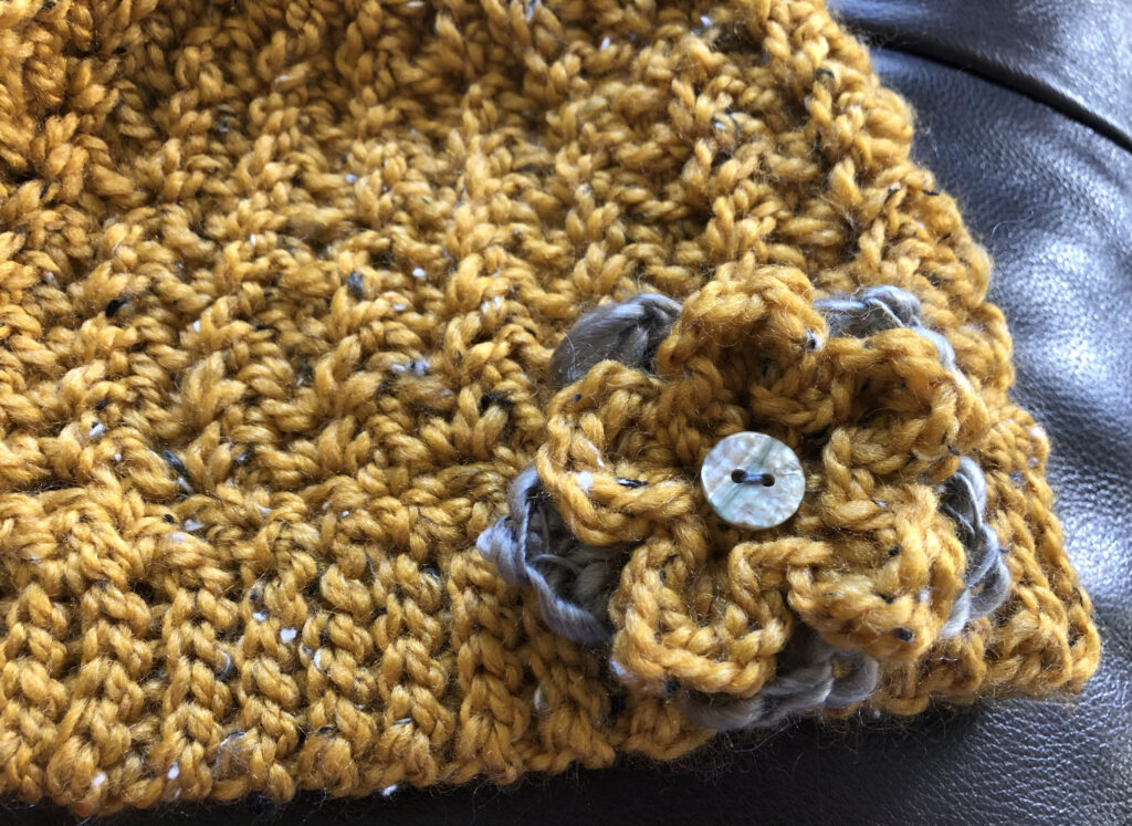 Chunky crocheted hat in a mustard colour with a double layered crocheted flower detail.