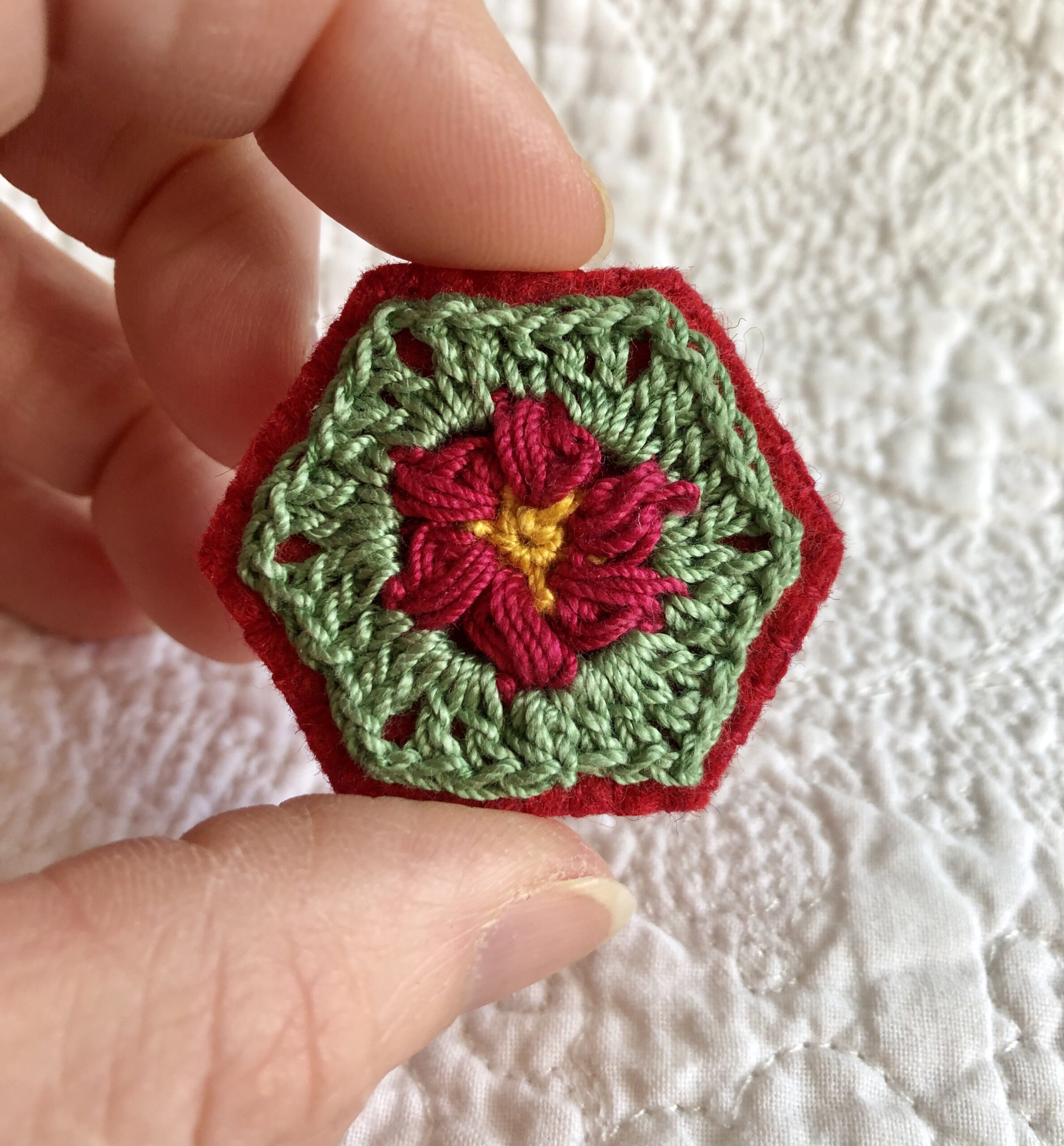 A hexagon shaped, hand stitched, felt and flower design crocheted brooch with locking brooch fixing.