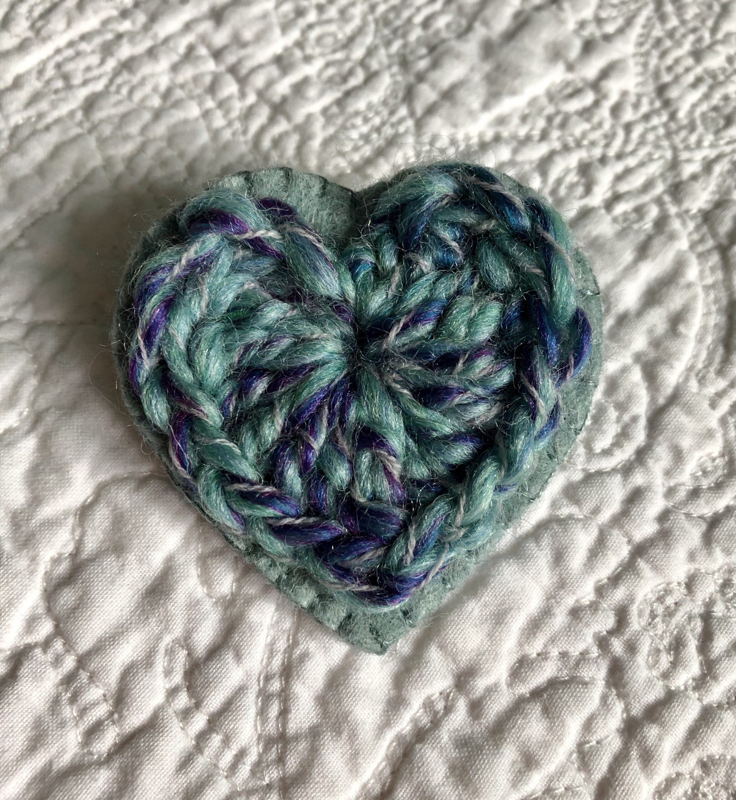 A crocheted heart on a hand stitched felt back with metal fixing brooch. Approximate size 6cm width x 6cm height.