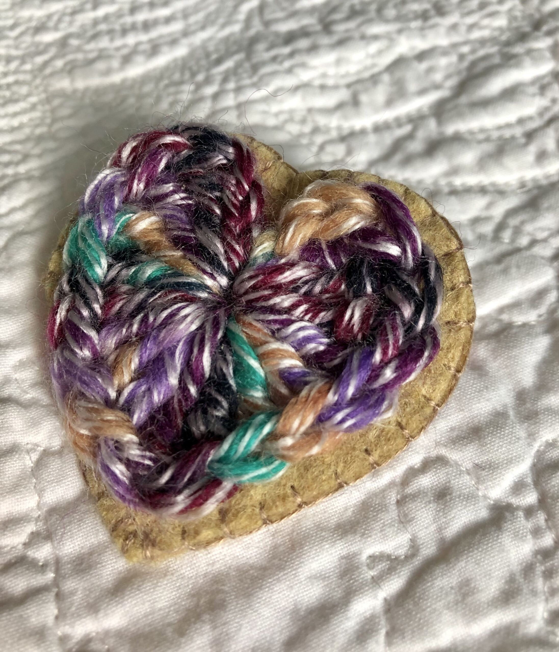 A crocheted heart on a hand stitched felt back with metal fixing brooch.