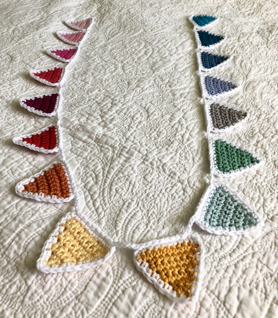 A rainbow of 16 individual coloured crocheted bunting flags. Handmade using 100% cotton yarn. Approximate length 125cm.