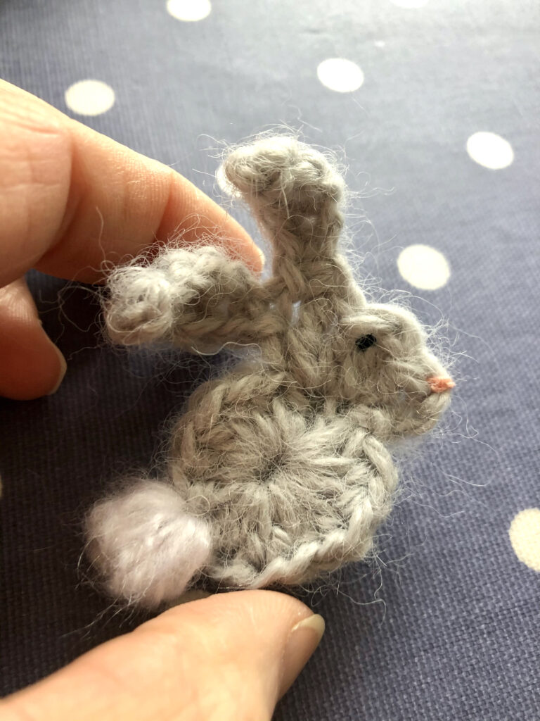 A handmade, crocheted grey bunny with white tail brooch.