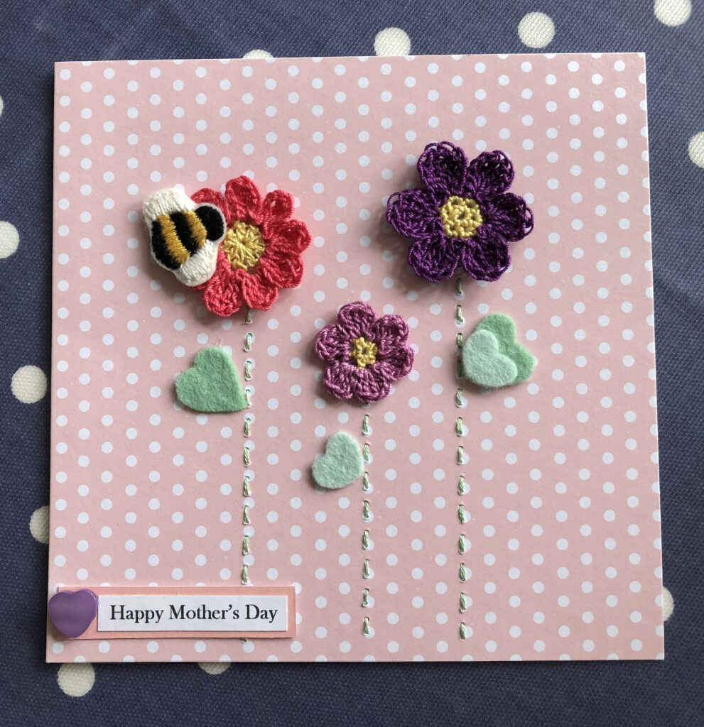 A hand embroidered and crocheted greetings card with bumble bee, flowers and a personalised tag.