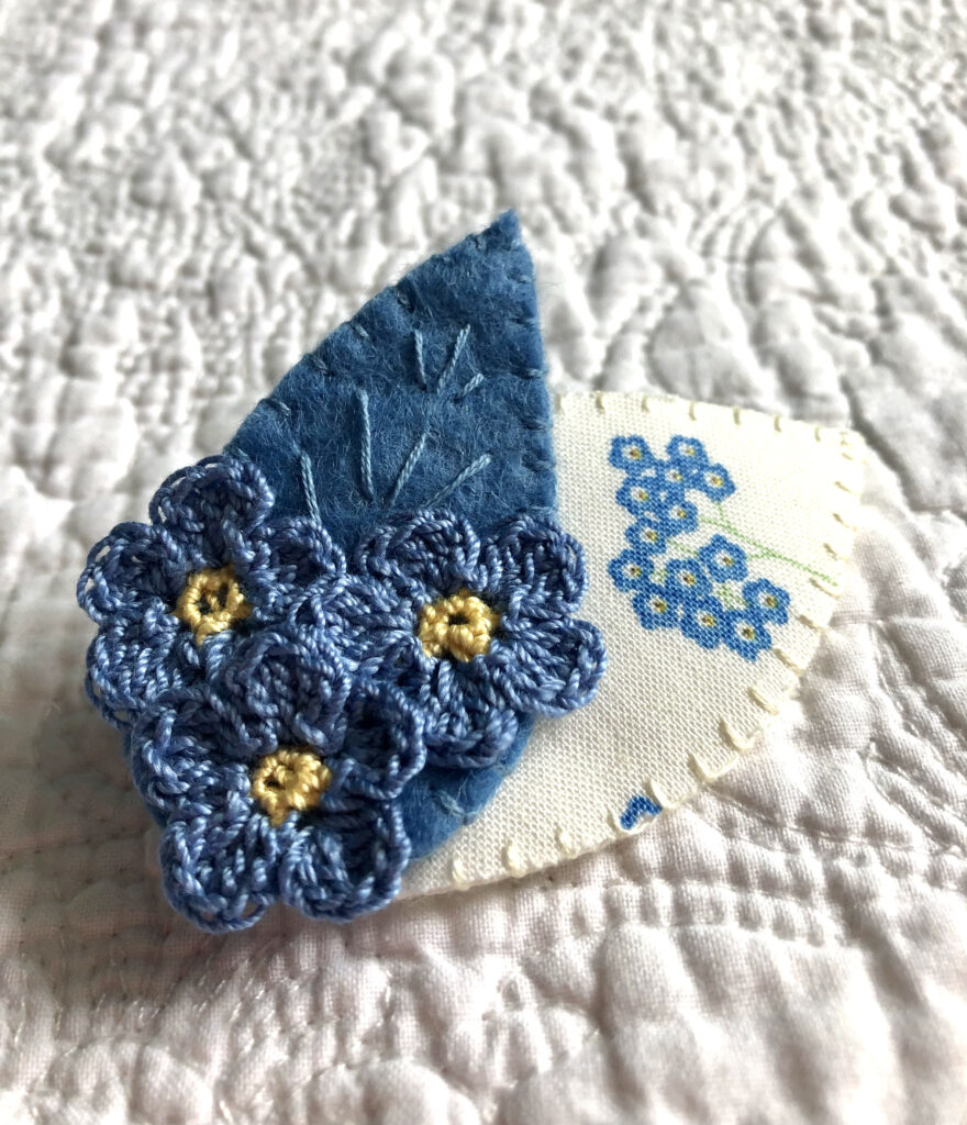 Posy of 3 Forget-Me-Not crocheted flowers and two leaf brooch. 100% Cotton flowers with hand stitched felt and fabric leaves.