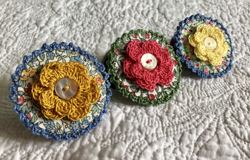A round brooch made using a patterned fabric background with a crocheted flower in the centre and  crocheted edging. Handmade using 100% cotton fabric and yarn. With button detail and a locking brooch fastening on a felt backing.