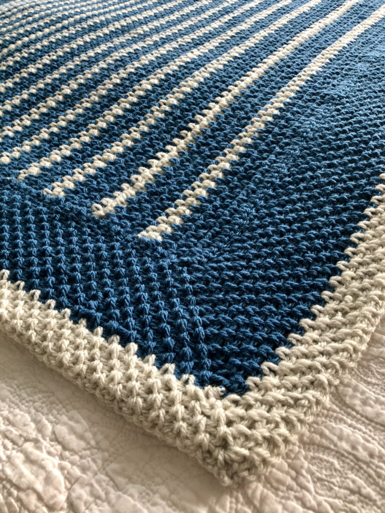 A handmade, crocheted blanket in light denim blue and light cream. Made with 80%Acrylic/20% Wool mix yarn.  Approximate size 92cm Width x 92cm Height.
