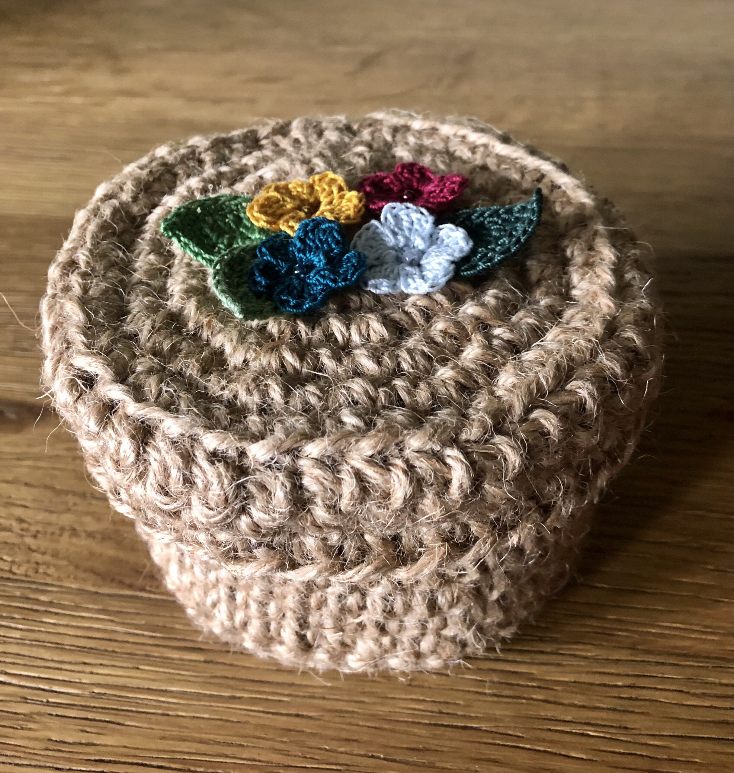 A handmade, crocheted 100% jute basket with lid. Decorated with 100% cotton crocheted flowers and leaves. Approximate size 7.5cm Height x 11.5cm width.