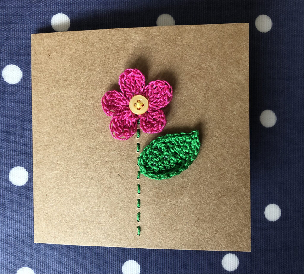 A single hand sewn and crocheted pink flower with button detail and green leaf on a brown greetings card. Left blank for your own message.