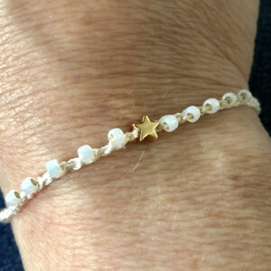 Single strand, fully adjustable bracelet with glass beads and gold metal coloured charm. Handmade using 100% cotton. Eco-friendly and fully recyclable.