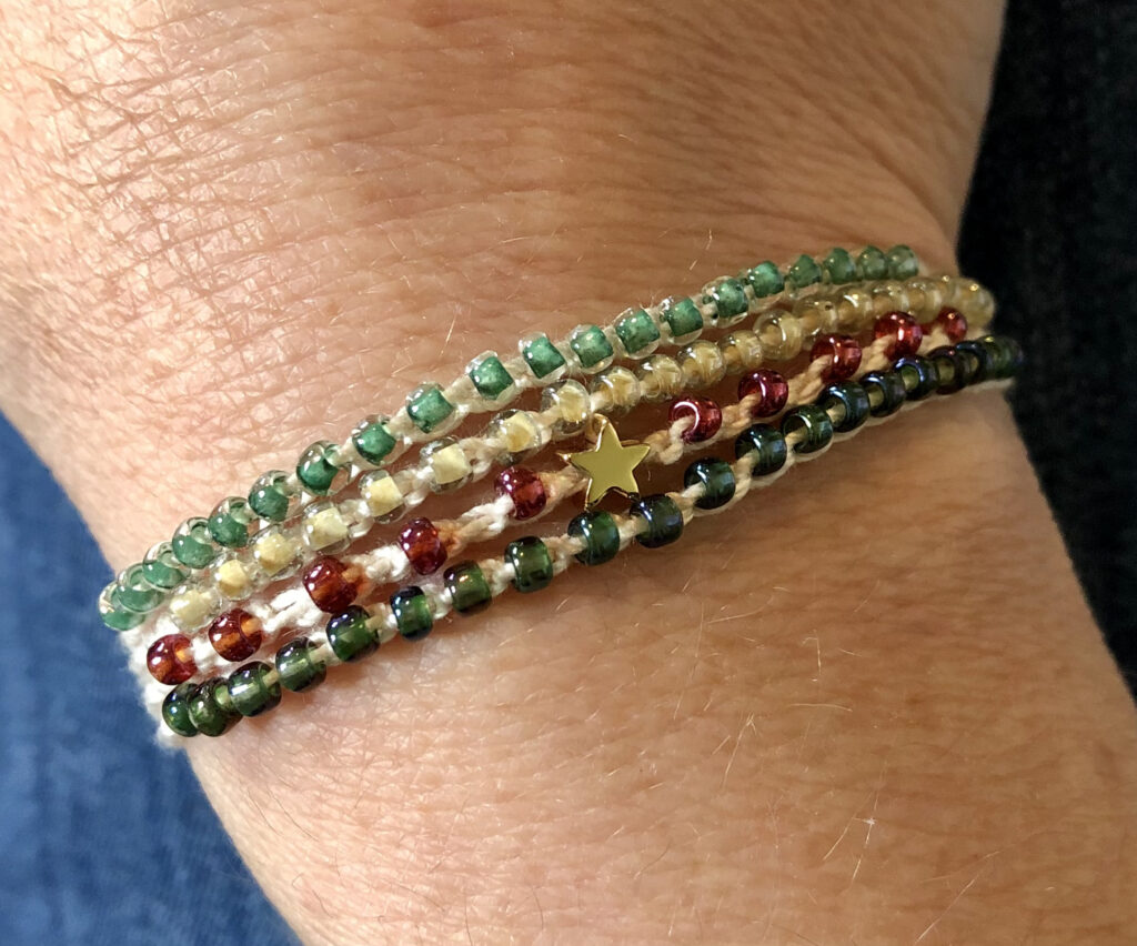 4 strand, fully adjustable bracelet with glass beads and gold metal coloured charm. Handmade using 100% cotton. Eco-friendly and fully recyclable.