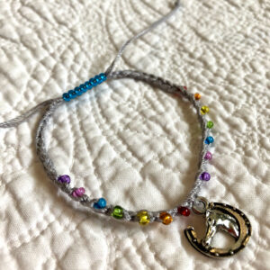 Single strand, fully adjustable bracelet with glass beads and silver metal coloured charm. Handmade using 100% cotton. Eco-friendly and fully recyclable.
