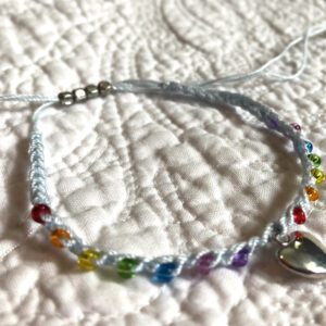 Single strand, fully adjustable bracelet with glass beads and silver metal coloured heart charm. Handmade using 100% cotton. Eco-friendly and fully recyclable.
