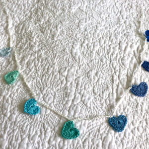 8 tiny crocheted hearts on a garland, in blues and greens. Made in 100% cotton.