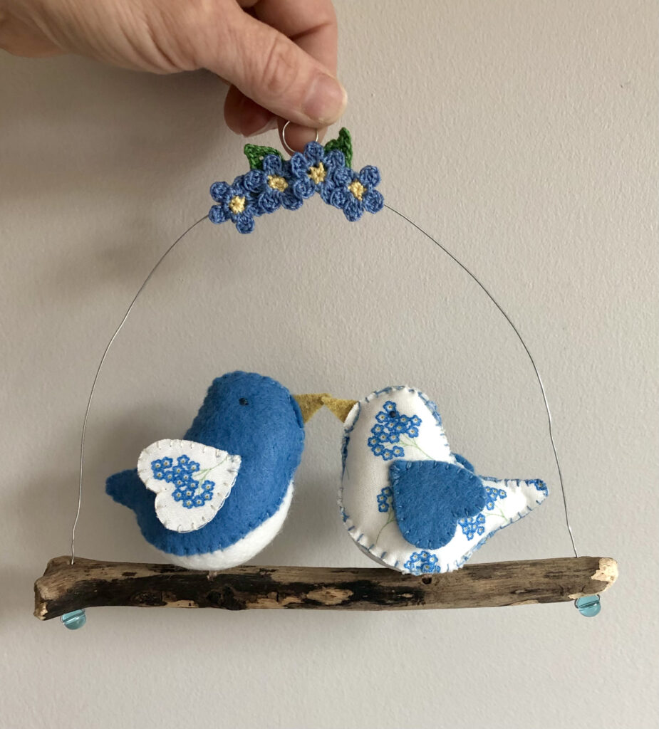 A pair of handmade little birds in Forget - Me - Not fabric and felt. These birds are sat on a natural driftwood perch with a wire hanger that is decorated with crocheted flowers and leaves.