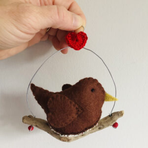 A single, medium sized, handmade little robin, made in brown felt with a cotton holly print fabric chest. This bird is sat on a natural driftwood perch with a wire hanger that is decorated with a crocheted red heart.