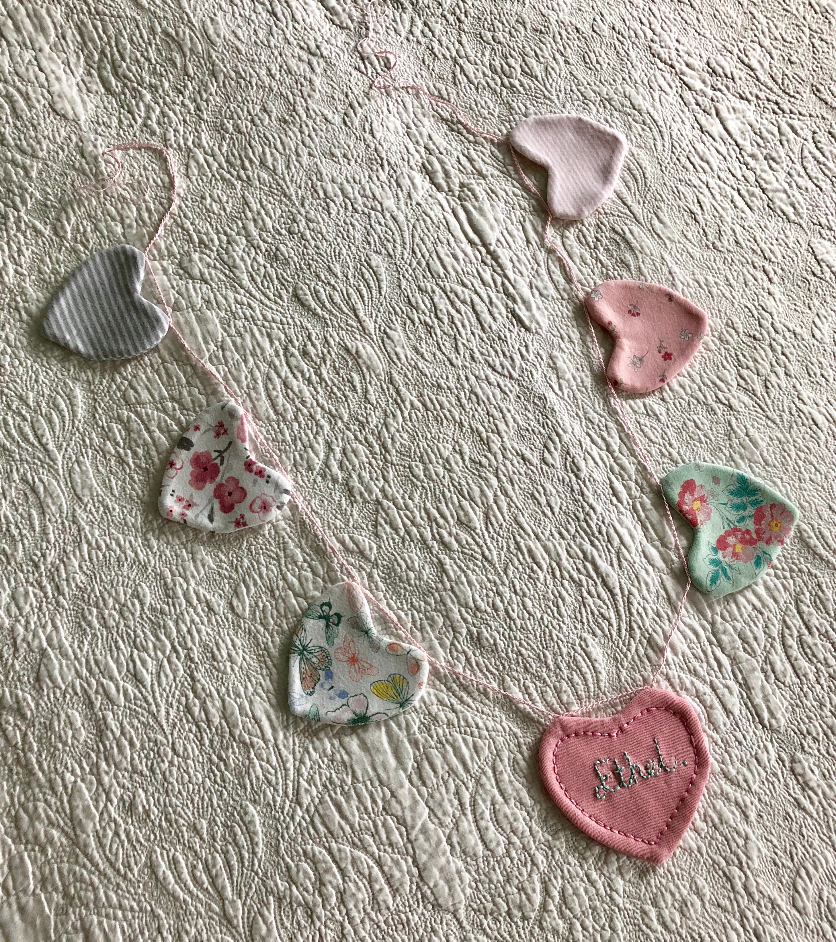 A keepsake hand embroidered heart garland made using a loved ones clothes.