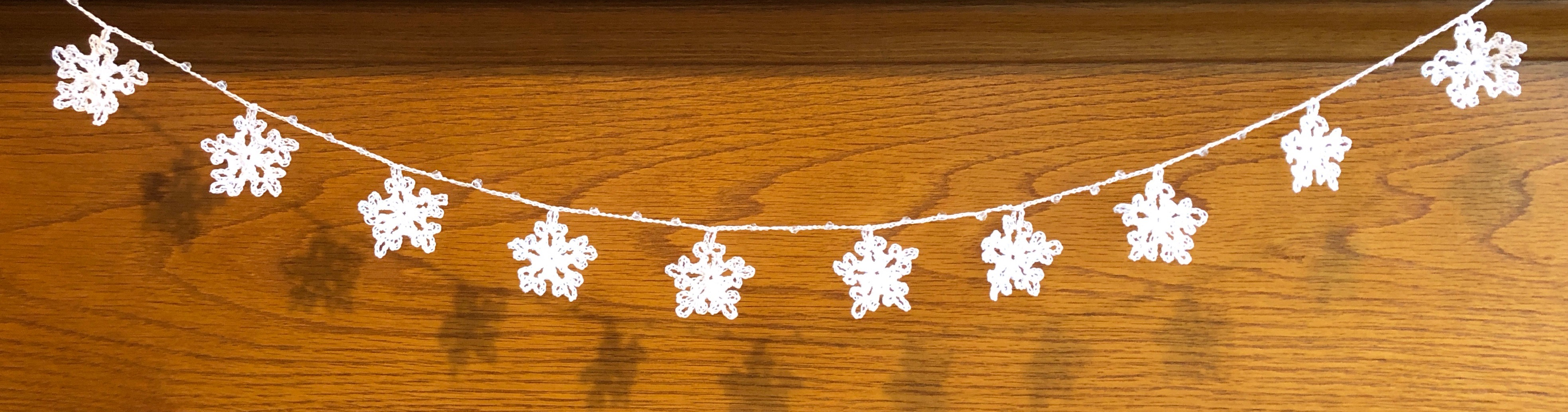 Handmade, crocheted, white cotton snowflakes and clear crystal style bead garland.