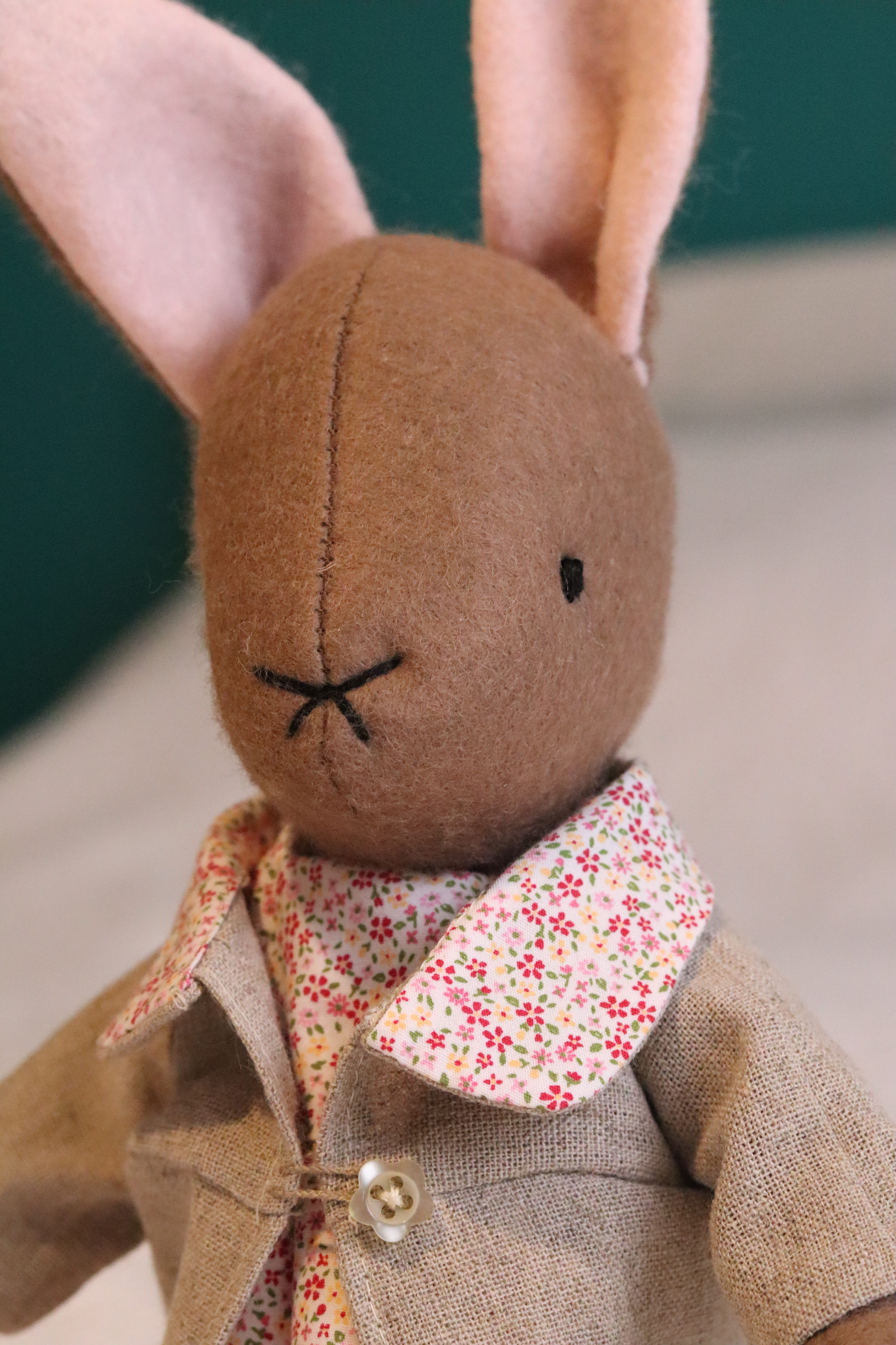 A handmade brown felt bunny rabbit with cotton floral dress and a natural linen coat with a hand embroidered name on her ear. Made using a pattern by Simone Gooding.