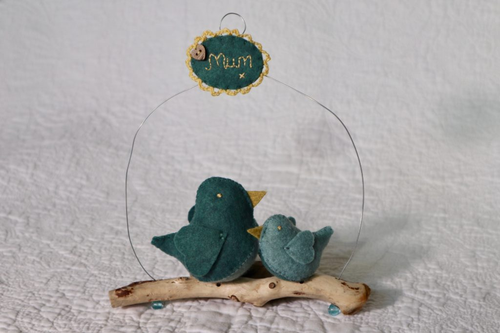 Two teal and green hand sewn felt birds sitting on a driftwood branch with a wire hanging hoop and hand embroidered plaque.