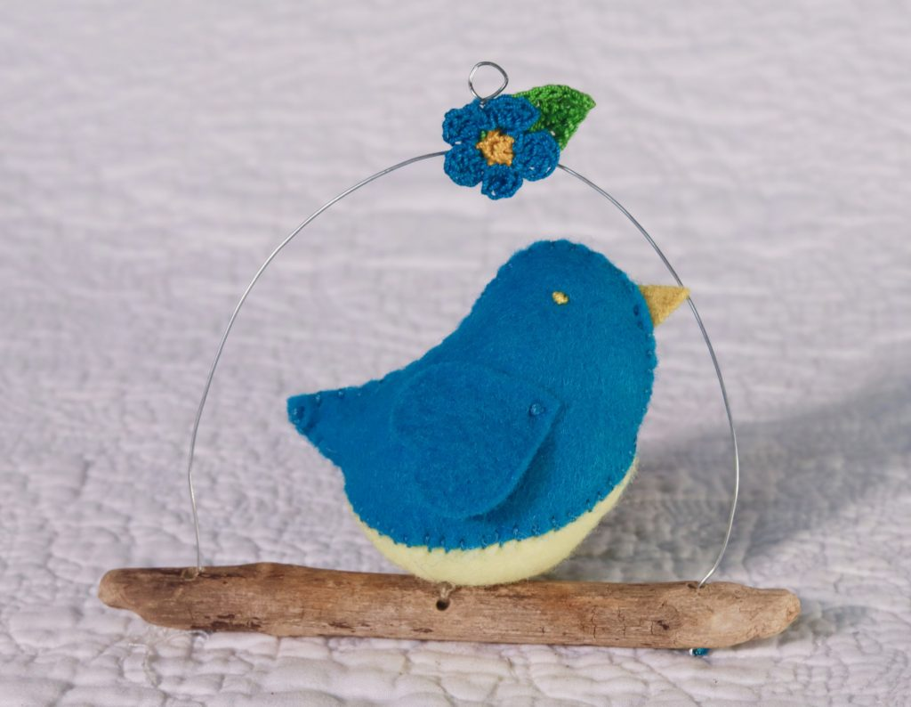 Single hand sewn felt bird sat on a driftwood branch with wire hanging hoop and small crocheted detail.